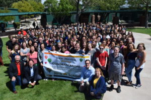 large group of students from East Mountain High School proudly display National Blue Ribbon School banner outside on a sunny day