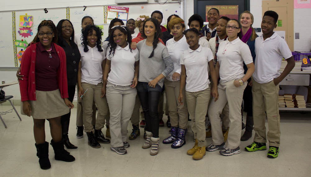 Rocsi posed for a picture with Ms. Lorraine Philyaw (ELA teacher, second on the left in all black) and the 8th grade class who had the most improved attendance during the challenge.